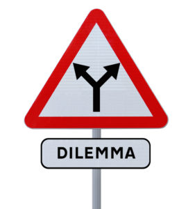 A road sign showing two arrows leading in different directions and a label below that says dilemma