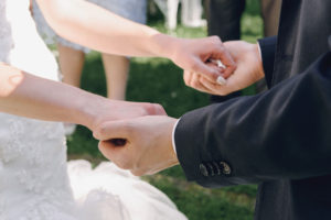 Couple holding hands during marriage ceremony – In sickness and in health, till death do us part