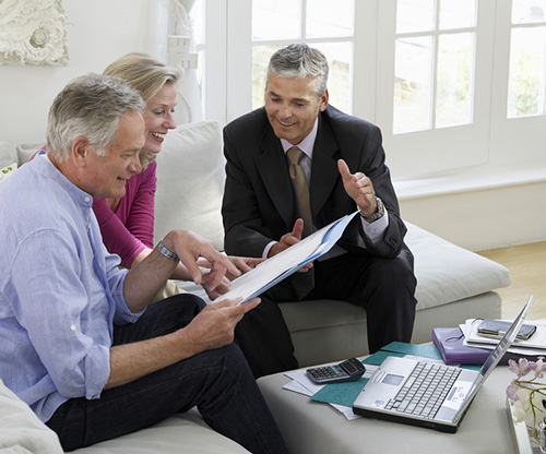 Couple sit at home with Financial Advisor - Does The Average Investor Need A Financial Advisor?