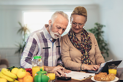 Senior couple checking retirement accounts at home - annuities and retirement