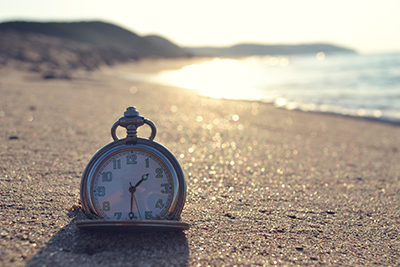 Pocket watch sitting on the sand at the beach