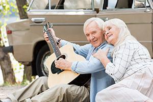 Senior Couple Enjoying the Park Playing Guitar
