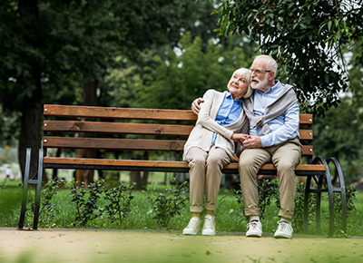 Older couple sitting on a park bench enjoying the day
